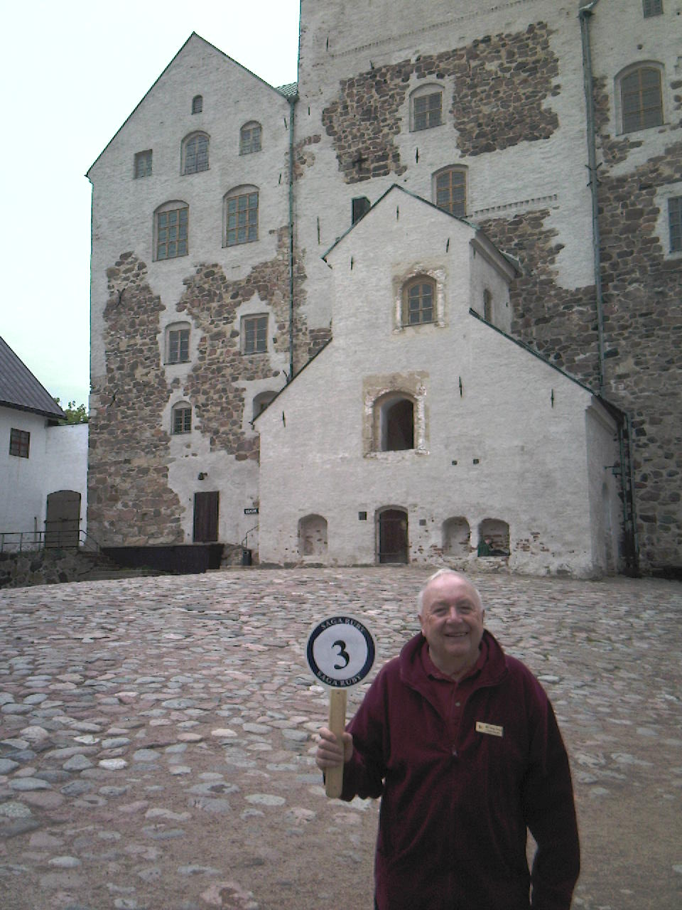 George in his ruby red tour escort's uniform at Turku castle